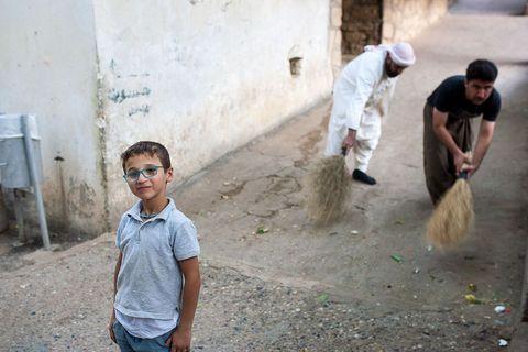 Mali Jezid na ulicama svetog grada Lališa, kojeg stariji ritualno čiste iza njegovih leđa